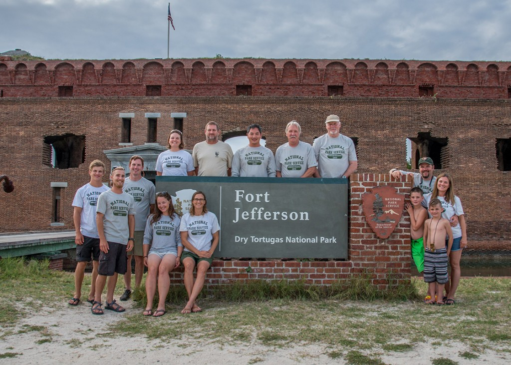 The members of expedition DRTO-SRC-0188 gather in front of Fort Jefferson's welcome sign. From left to right: Dylan Hardenberg, David Morgan, Jeneva Wright, Susanna Pershern, Jess Keller, Charlie Sproul, Bert Ho, Koza, Jim Bradford, Brett Seymour, Elizabeth Seymour, and Cameron and Chase Seymour.