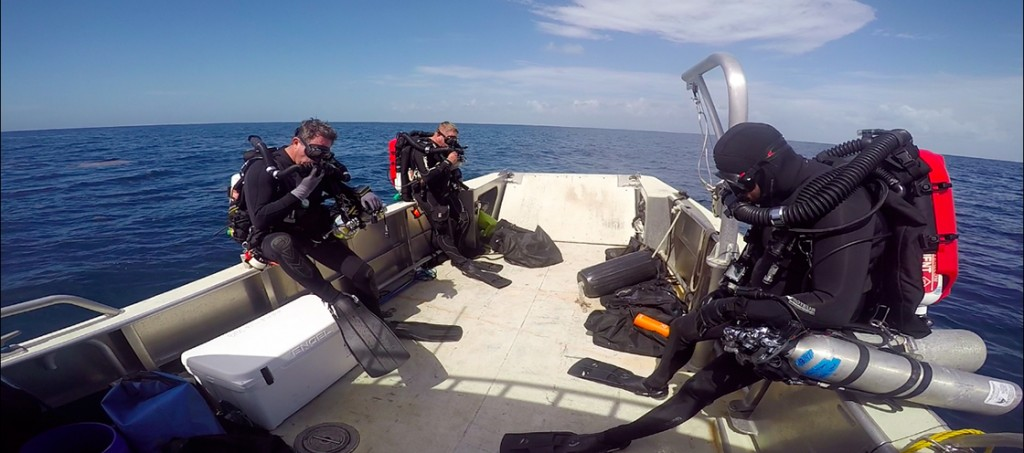 Prior to entering the water on a closed-circuit rebreather (CCR), divers must first pre-breath their gas mixture to make sure everything is functioning properly. From left to right: Steve Sellers (the NPS's DSO), Dave Conlin (the SRC's Chief) and Brett Seymour (the SRC's  Deputy Chief).