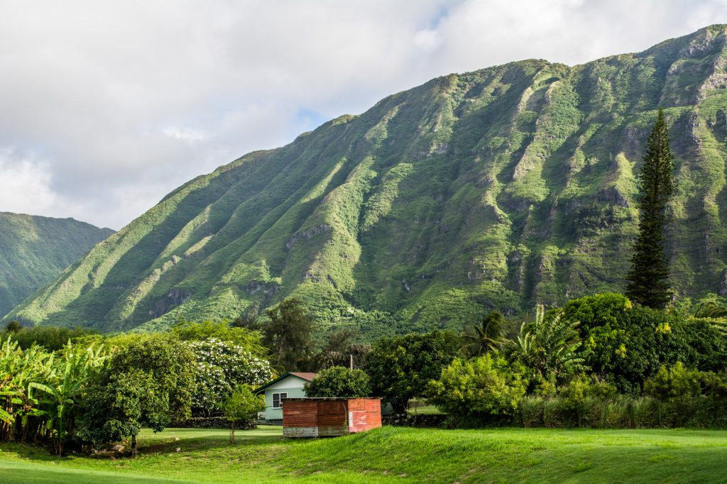 A resident's home sits in front of a backdrop of Kalaupapa's infamous sea cliffs.