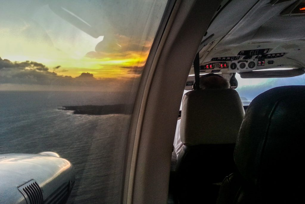 As the sun rises, Kalaupapa emerges into view on the horizon aboard the Makani Kai flight.
